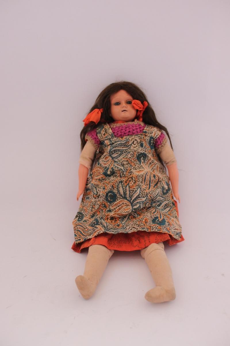 Celluloiddocka med brunt hår. Huvud och armar i celluloid, överkropp och ben i textil. Med riktigt hår och blundögon i porslin iklädd en röd klänning med blommönster. Virkad tröja och förkläde. Orangea rosetter i håret.