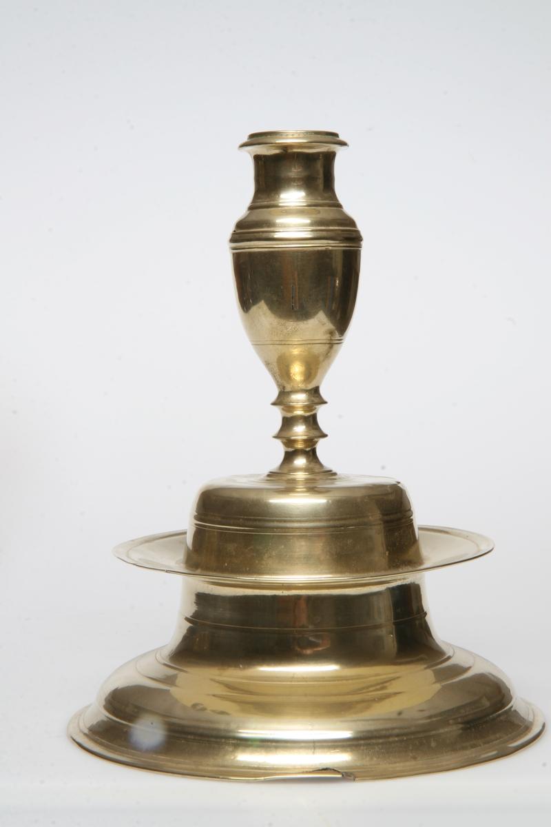 Kraftig profilert pipe, rund fot, plate mellom pipe og fot. Inngraverte ringer.