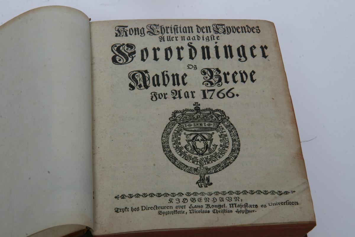 """Innbundet i skinn med gulltrykk. """"Kong Christian den Syvendes allernaadigste Forordninger og Aabne Breve"""" 1766-1771. København u.å."""