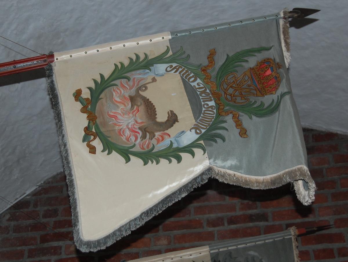 Oljemaling på blå og hvit silke. Blå og hvite silkefrynser. Drage hvilende på flammer omgitt av bladkrans kronet av Fredrik IVs speilmonogram. Montert på fanestand av bøk, delvis kannelert, beiset rødbrun, beslått med jernskinner og -nagler.