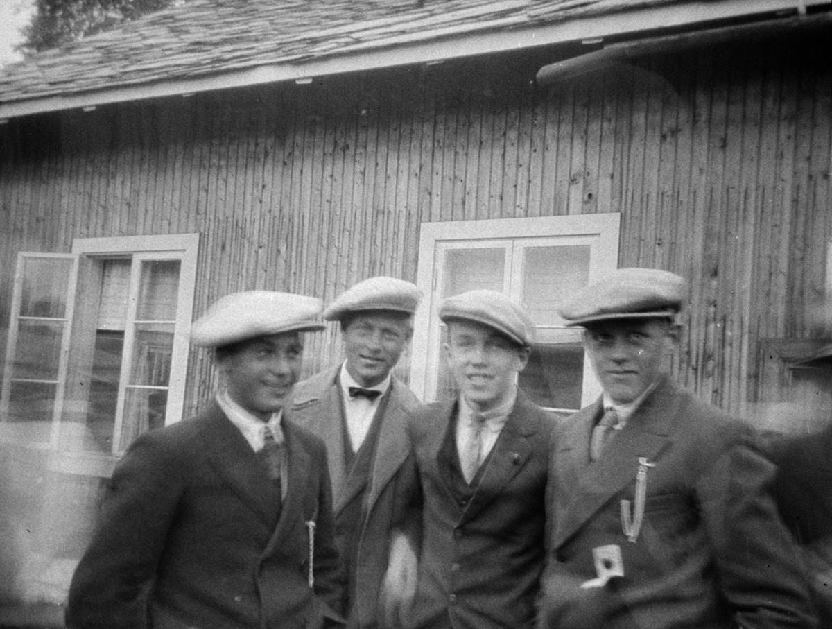Fire unge gutter i skyggeluer utenfor ei hytte.