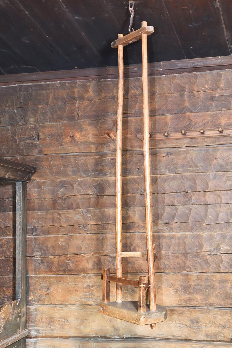 Gunga för barn av trä, med S-krok av järn för att hängas i taket. Halvcirkelformat säte i massivt trä, 2 störar på var sida av sätet går upp till tvärslå som fäster med krok vid taket. Ryggstöd av böjd spjäla och upprättstående slå. Framtill på sätet bildar två upprättstående slåar samt däremellan en löstagbar tvärslå en grind, för att hindra barnet från att trilla ur.