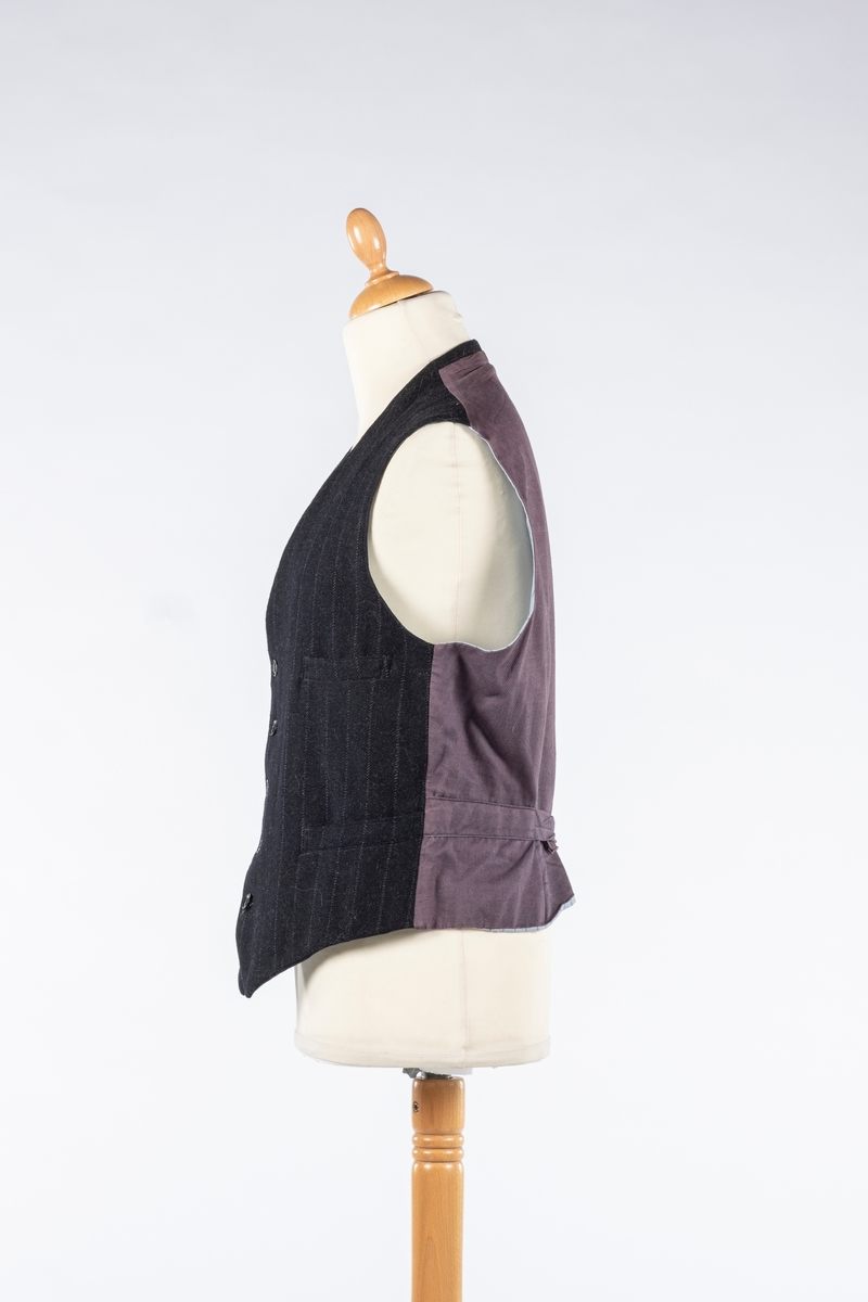 Vest i ull med stripete mønster og spisse hjørner. Den har grå bomullsrygg og er foret med blå stripete stoff. Den kneppes med fem knapper. Den har tre lommer i front.