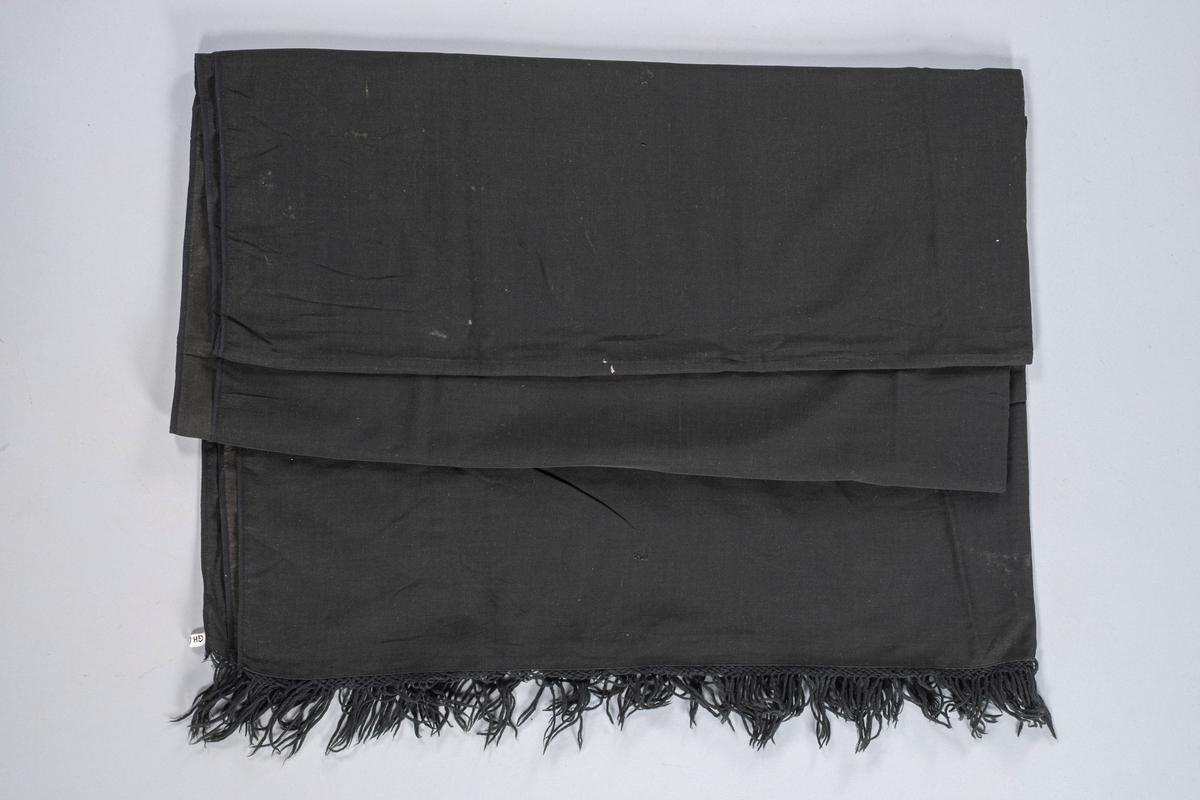 Rektangulært sort sjal i bomull. På begge kortsidene er det en flettet kant med knyttede frynser ytterst. Sjalets underside er litt lysere enn oversiden.