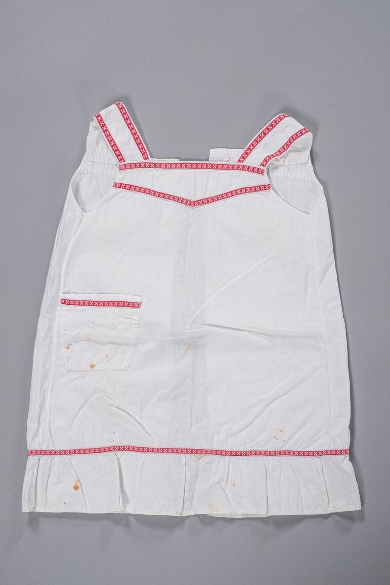 Forklekjole til barn uten ermer. Den har åpning bak og kappe nederst. I front er det en lomme på høyre side. Forkleet er dekorert med rødt bånd med hvitt mønster som er sydd på langs kantene på seler, hals, lomme og i kappelinningen.