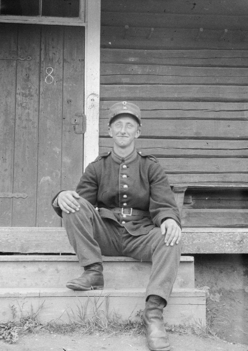 Soldat i  uniform på en trapp. Dør med tallet 8 bak.