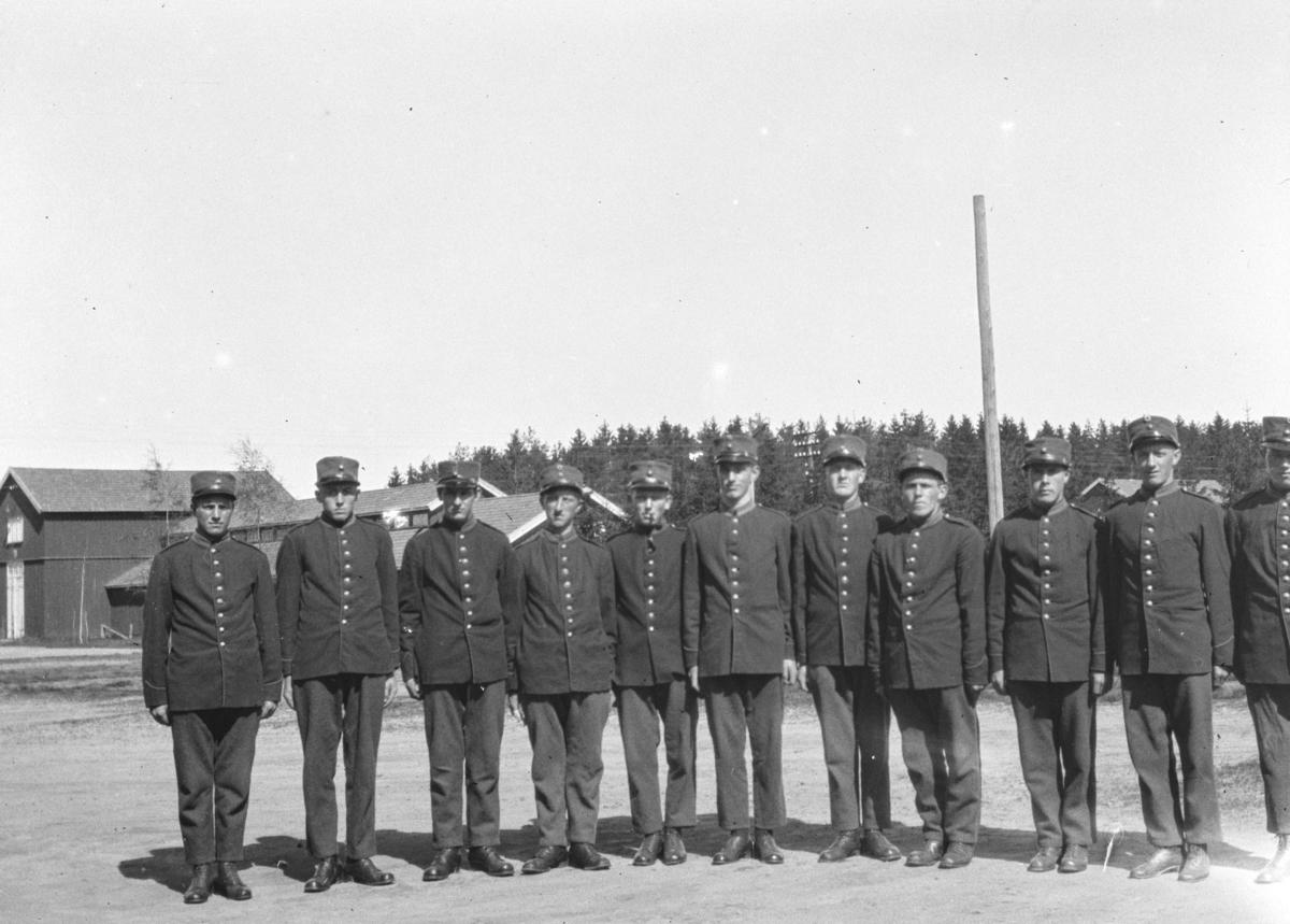 11 soldater oppstilt i en militærleir.