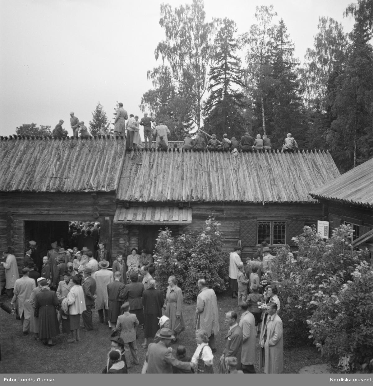 Motiv: (ingen anteckning) ; En folksamling står kring en midsommarstång, en folksamling vid ett hus, en kyrkbåt ros av kvinnor och män i folkdräkt, en folksamling står vid en brygga med en kyrkbåt.