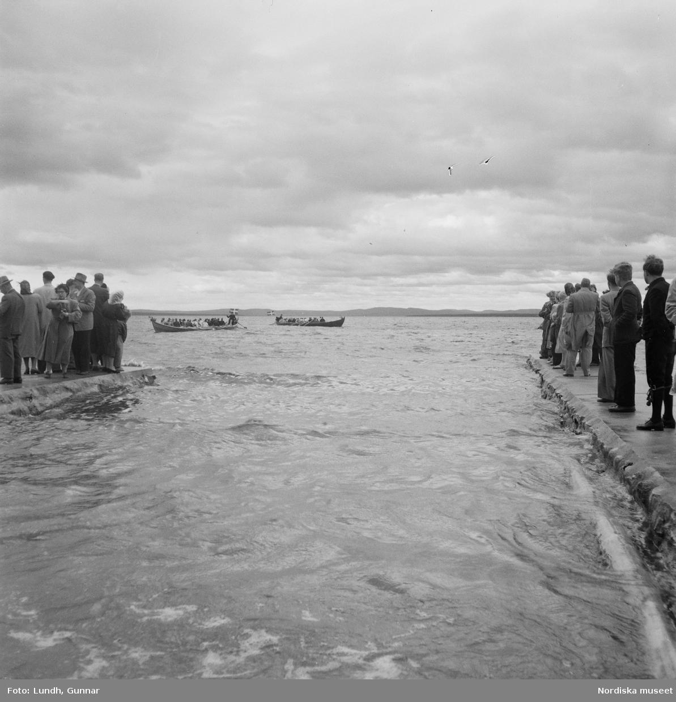 Motiv: (ingen anteckning) ; En folksamling står vid en brygga med två kyrkbåtar, kvinnor och män ror kyrkbåtar i samband med midsommarfirande.