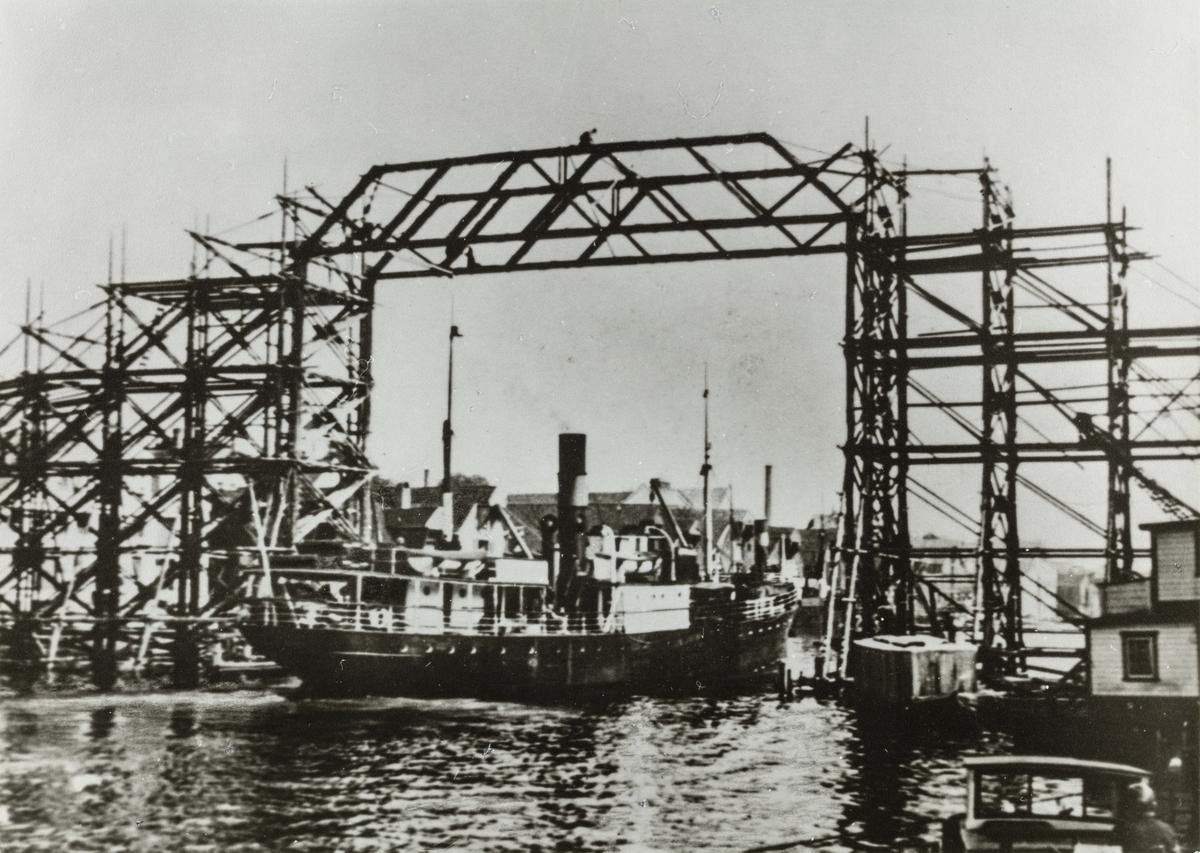 """D/S """"Karmsund"""" passerer under Risøybroen under bygging, ca. 1938."""