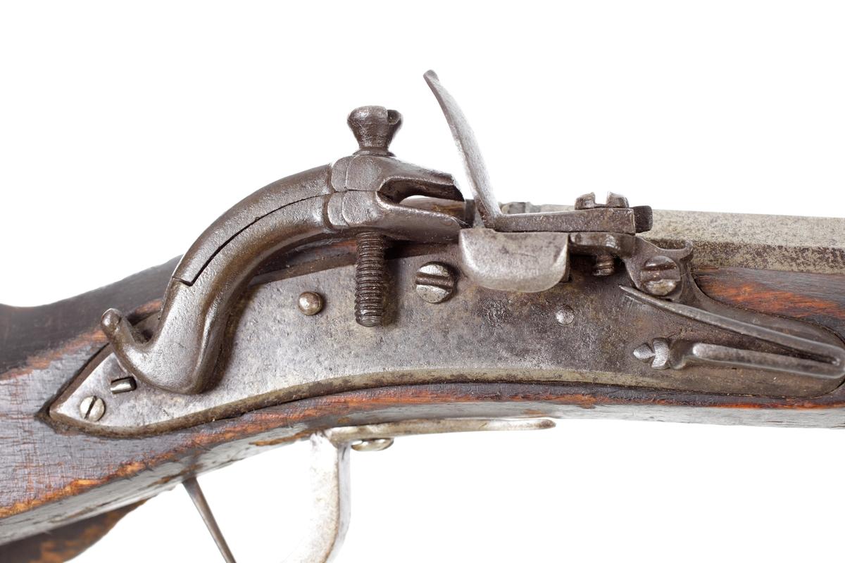 Snapplåsgevär av svensk typ försedd med ett s.k. lägglås. Stocken är smal och tunn. Laddstocken är av järn och sitter inskjuten i tre rörkor i laddstocksrännan. Näsbeslaget är tillverkat av horn, och kolven har en muskötliknande form, något trekantig i formen och tvärt avhuggen baktill. På högersidan är kolven försedd med ett urgröpt kolvfack som täcks av en rundad skjutlucka. Bakplåten är tillverkad av järnplåt och har en järnkula längst upp. Pipan är rund med en kraftig avslutning vid mynningen där den är åttakantig. På pipans översida finns det mässingsinläggningar som dekoration där även kornet är i mässing. Den är räfflad invändigt med en innerdiameter på ca. sex m.m. Inskrivet i huvudkatalog 1870.