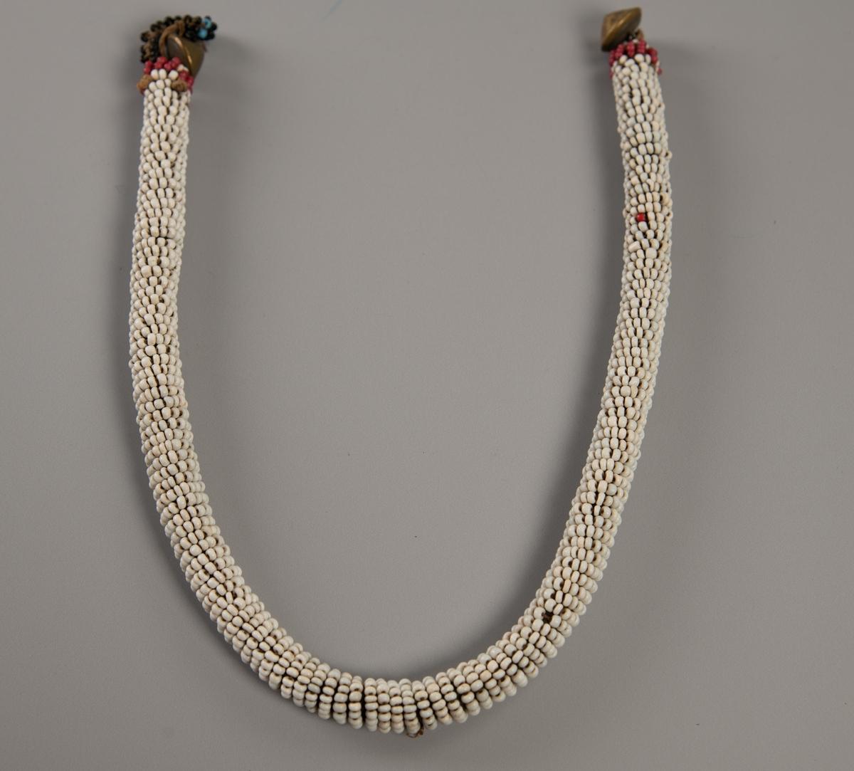 Hode- eller leggpryd. Zulu. Perle  snor med   messing  knapper. Hvit litt tykk perlesnor med en rød ring ytterst i hver ende,  utenfor  denne en spiss messingknapp og i den ene ende en hempe av  sorte og  lysblå perler.