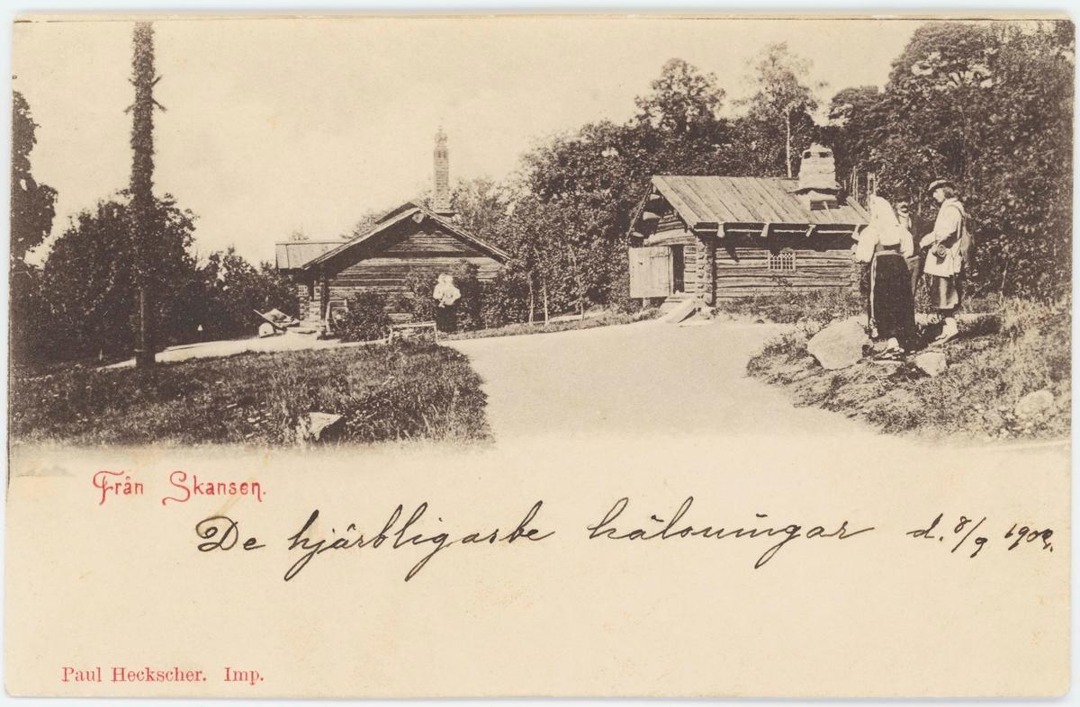 Vykort med motiv från Skansen. Morastugan och Orsastugan (Hackstugan). I förgrunden troligen två dräktdockor.