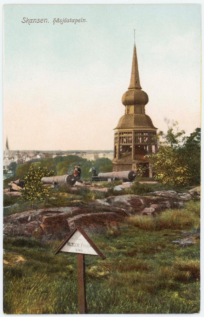 """Vykort med motiv från Skansen. Håsöstapeln. Kanoner och en vägskylt """"RutgerFuchs väg""""."""