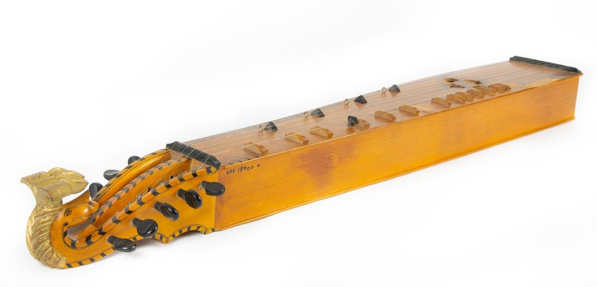 Instrumentkassen har dekor av sorte felt langs kantene og streker i sikksakk-mønster. Mønster med prikker mellom strekene. Rankedekor om lag midt på instrumentet. Åtte metallstrenger. Halsen ender i løvehode som er dekorert med gullmaling.   Kasse av tre med metallhengsler og lærhåndtak.