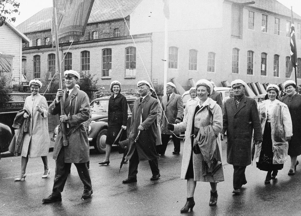 """Blandakoret """"Toneveld"""" med fane i 17. mai tog framfor bygningane til Serigstad Maskin a/s. Fana er teikna av Ola Nordsletten. Etterat koret vart oppløyst ca 1981, ga dei fana til Time bygdemuseum."""