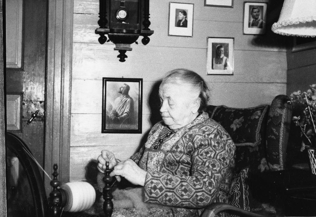 Pauline Frøyland (11.9.1884 - 12.4.1969) ved rokken i stova på Frøyland. Sjå også 1990.1TIM.2.001