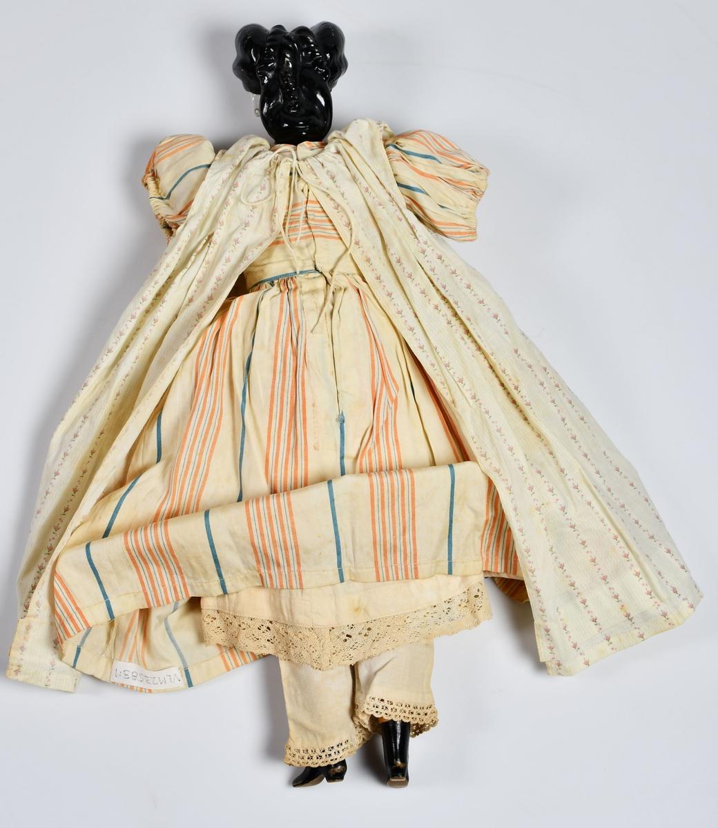 Flickdocka med kläder. Dockan har huvud av porslin och kropp av hårdstoppat tyg. Benen nedanför knäna och fötterna är av trä. Armar saknas. Dockan är klädd i byxor och linne, underkjol, klänning och förkläde. Allt i bomull.   Dockan var en gåva till Lisa Svartz (1881 - 1904), (äldre syster till Nanna Svartz) från familjen Sjöqvist bosatt i Västerås.   Dockan heter Jacquette. Kläderna är sydda av Anna Svartz, mor till Lisa Svartz.   Till dockan hör en underklänning och ett par underbyxor i vit bomull, invnr 23579.   Tillverkningstid: ca 1885.