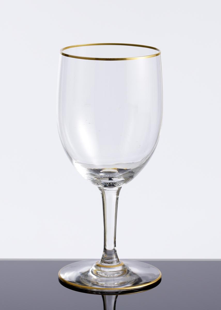 Vinglas med guldförgylld rand kring mynning och fot. Ofärgat klarglas.