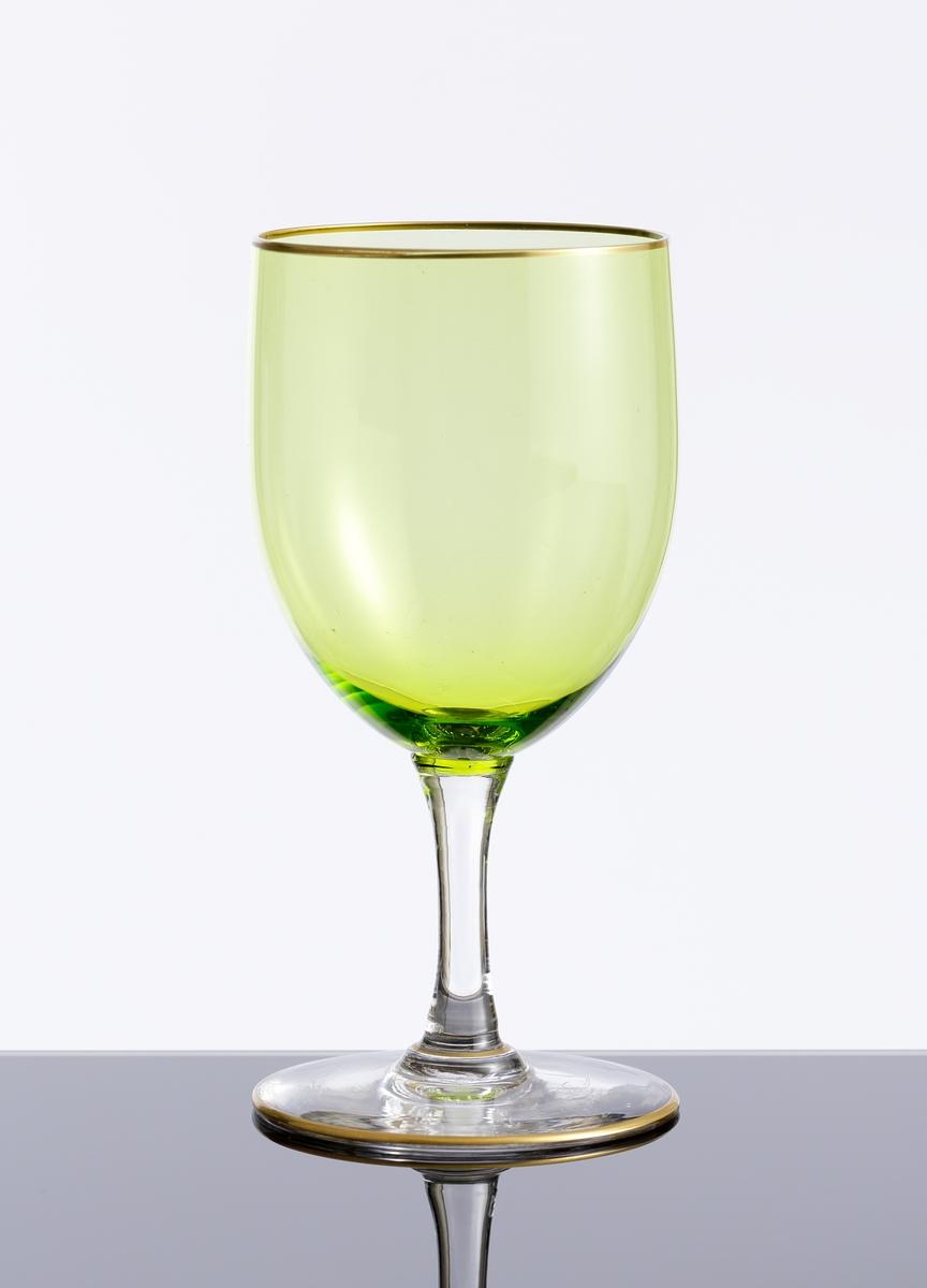 Vinglas med guldförgylld rand kring mynning och fot. Gröntonad kupa. Fot och ben i ofärgat klarglas.