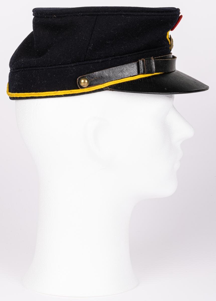 """Militär mössa från Hälsinge regemente, stämplad """"HR"""" under krona, samt """"14 R"""" och """"No 3050"""".  Storlek 56 1/2. Av mörkblått tyg, med smalt gult band nertill runtomkring, lilla riksvapnet framtill samt rött märke för komp. siffra. Höjd 10cm, något framåtlutande."""