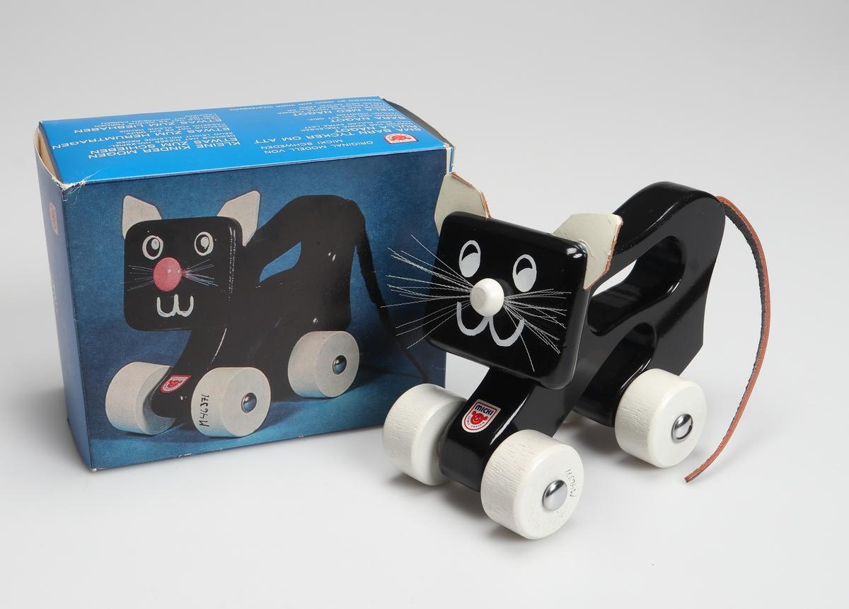 Svartlackerad katt av trä, med kroppen utformad som ett handgrepp. Den har fyra vita hjul, vita öron, nos samt morrhår av plast. Svansen består av en bit läderrem.  Den är förpackad i en blå pappkartong med bild och text på svenska, tyska och engelska.