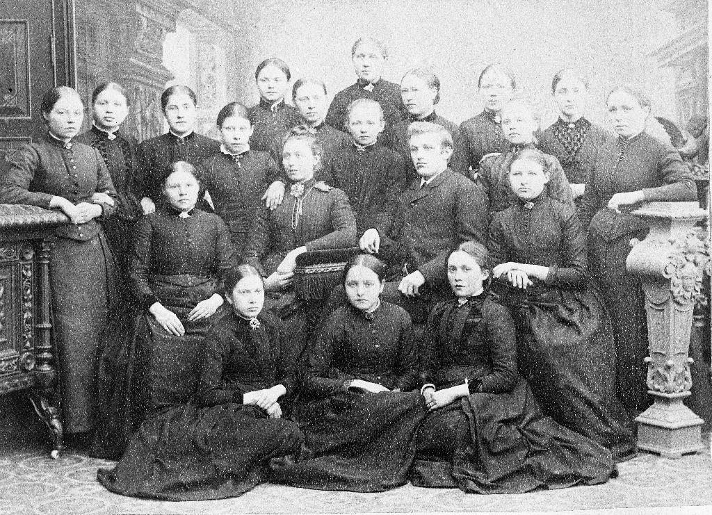 "Dette er første kull av ""Hjemmets Minde"" som vart halde i Time 1891 (?) Ståande til høgre er Kirsten Hognestad (30.4.1876 - ) g. Laland. Ho var mor til Gudrun Laland (informant). Andre som ho kjende att var Tora Wiig f. Bryne (mor til Ola Martinson Wiig) og kona til Peter Nilsen Aarrestad, ho var fødd Njølstad."