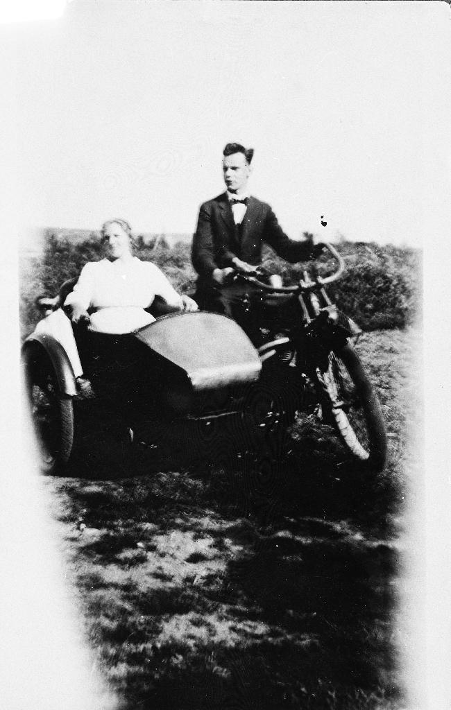 Motorsykkel med sidevogn. Personane er ukjende.