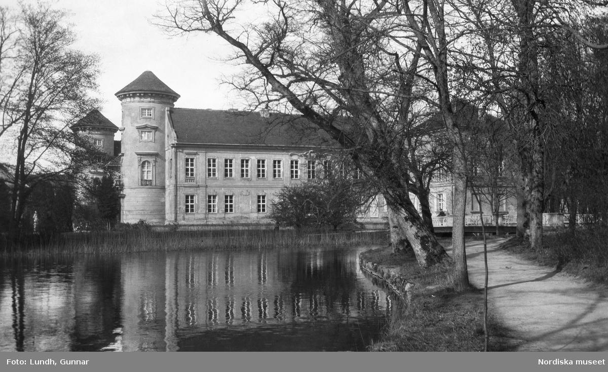 """Motiv: Utlandet, Märkische Schweiz 102 - 108, Rheinsberg 109 - 113 ; Landskapsvy med en kvinna som sitter på en bänk under ett runt vasstak, exteriör av ett slott, anteckning på kontaktkarta 110 """"Märkische Schweiz""""."""