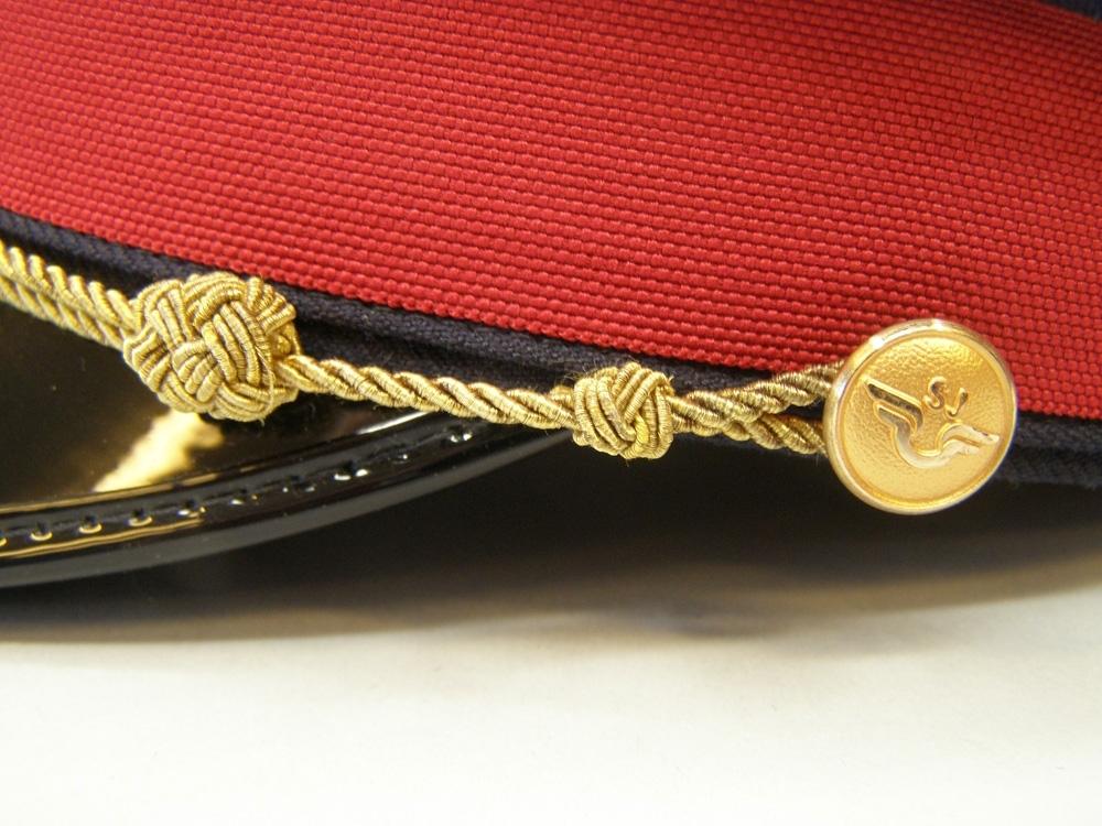 Skärmmössa med lågt kapell av vintertyg och rött mössband. Guldfärgad stormträns, guldfärgade (1991) mösstränsknappar, samt mössmärke av 1991 års modell.