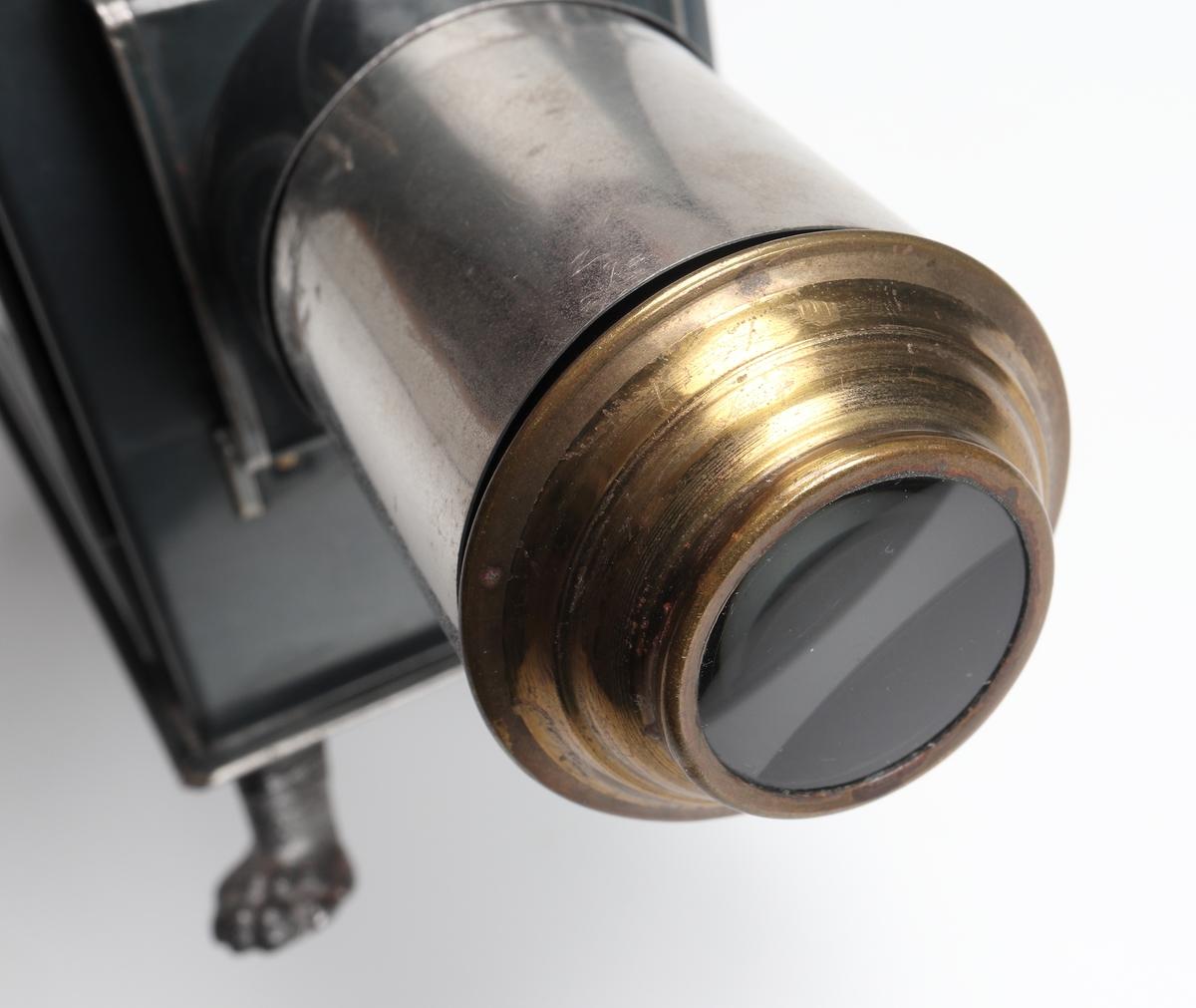 """Laterna Magica, leksaksprojektor tillverkad av blåanlöpt bleckplåt. Objektivet är skjutbart, med förnicklad hylsa. På projektorns sida finns en dörr där ljuskällan insättes, samt ovanpå den en vinklad rökhuv. Ljuskällan består av en enkel fotogenlampa.  Hela projektorhuset bärs upp av fyra fötter i pressad plåt. På dörrens sida finns ett ett förnicklat emblem med bokstäverna: """"GNB"""". """"Filmerna"""" eller bilderna till projektorn består av 22 st målade rektangulära glasbitar (18 x 5 cm) som har följande motiv: Snövit, Tummeliten, Törnrosa, Rödluvan, Jesu liv, Gamla Testamentet, Askungen samt Jesu korsfästelse."""