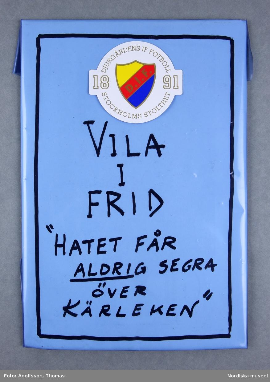 1 styck inplastad pappskiva  i ljusblått med Djurgårdens IF:s emblem i blått, rött och gult.   Längd 24 cm. Bredd 17 cm.  2019-03-01 Cecilia Hammarlund-Larsson/Lena Kättström Höök
