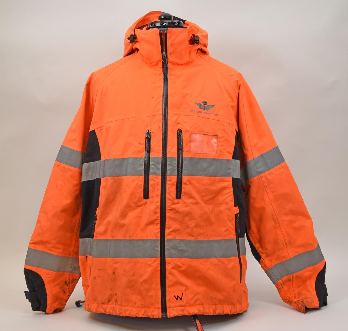 En arbetsjacka, varseljacka, storlek XL. Jackan är orange-aktig i färgen (typiska varselfärgen) och har två  reflexlinjer som går runt hela jackan. På slitytor som armbågar och rumpa har jackan svart textil. Jackan har tre dragkedje försedda fickor på utvändigt.