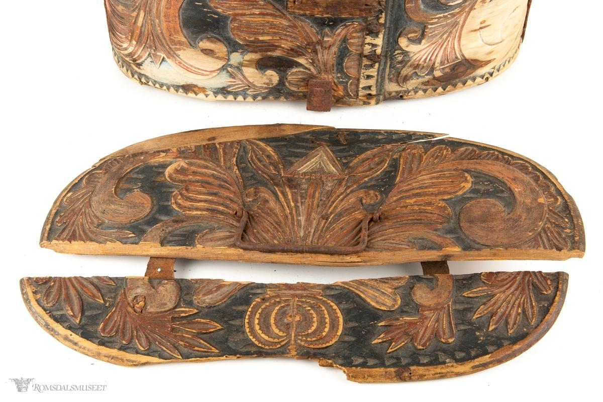 Store C- formede akantusranker med lange, slanke blader, er skåret inn i trosken. Selve mønsteret er i flatskurd, med karveskurdteknikk på bladene. Stor symmetrisk liljeform med akantusranker og blader på lokket. Tannbord øverst og nederst på trosken.