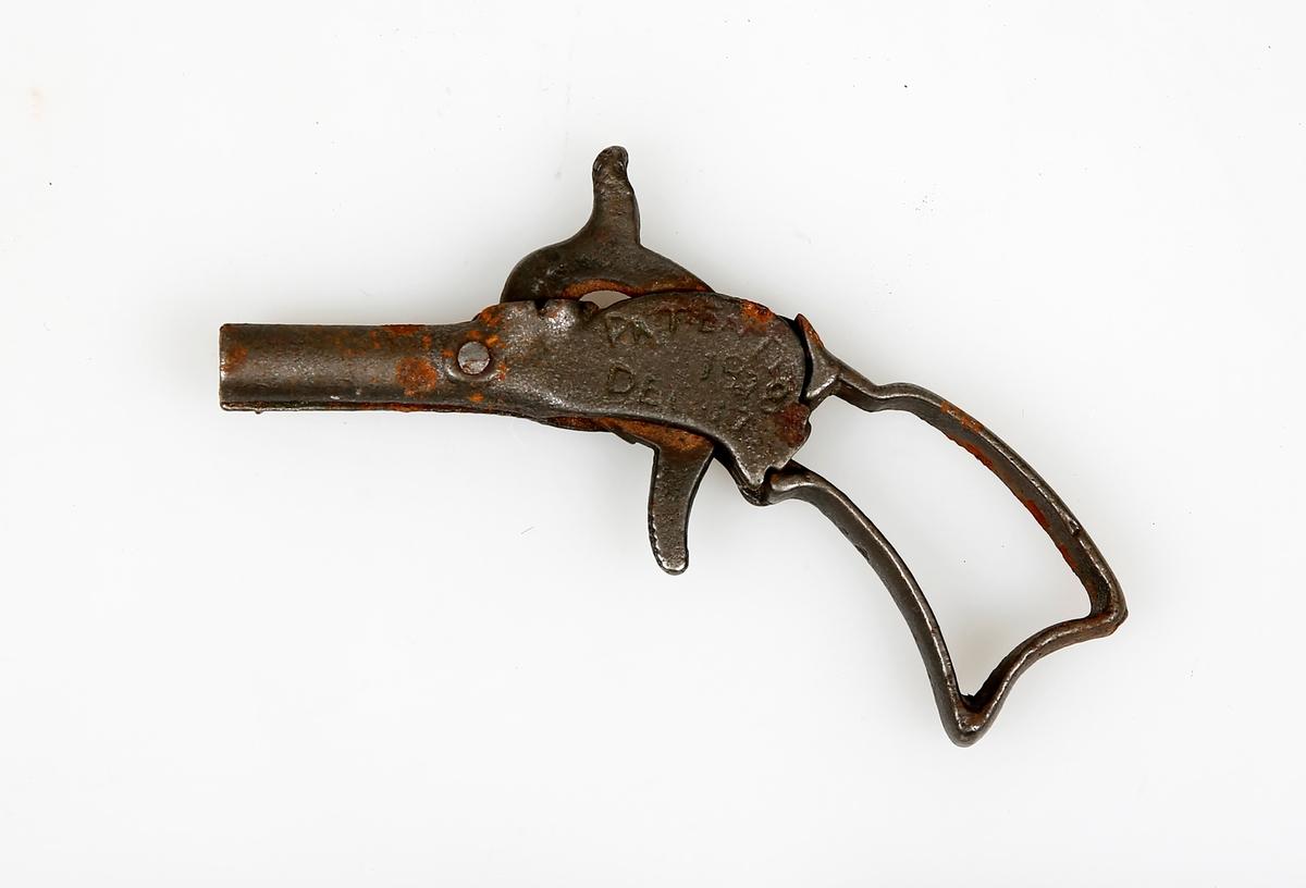 Liten lekepistol i metall med hane som kan spennes.