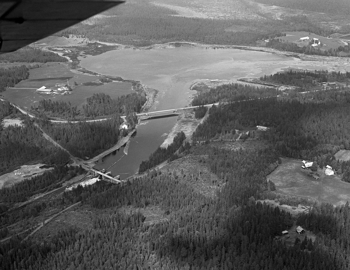 Osdammen. Tømmeret flyter mot dammen. Området ved Valmen, den vika i den nordvestre enden av Osensjøen i Åmot kommune som leder mot sjøens utløp i elva Søndre Osa. Fotografiet er tatt fra fly. Det viser hvordan vassdraget var lenselagt, og hvordan tømmeret ble fløtt mot Osdammen. Bru. Flere gårder.