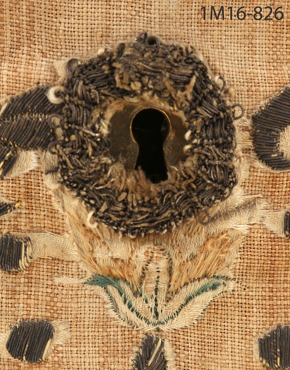 Skrin med kupigt lock, av trä, helt klätt med linnetyg, över detta siden med broderier av silvertråd och silke med blommotiv. Inuti klätt med sidendamast. Ett fack. Gångjärn och lås av metall, nyckel fattas, fötter av trä.