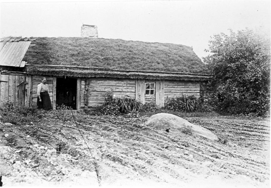 """Häggum sn.""""Statars-Krestin"""" framför sin stuga. Den låg vid Brismans (Boden) i Ranstad vid en grushåla höger om vägen. Stugan är riven. Där finns nu en sommarstuga."""