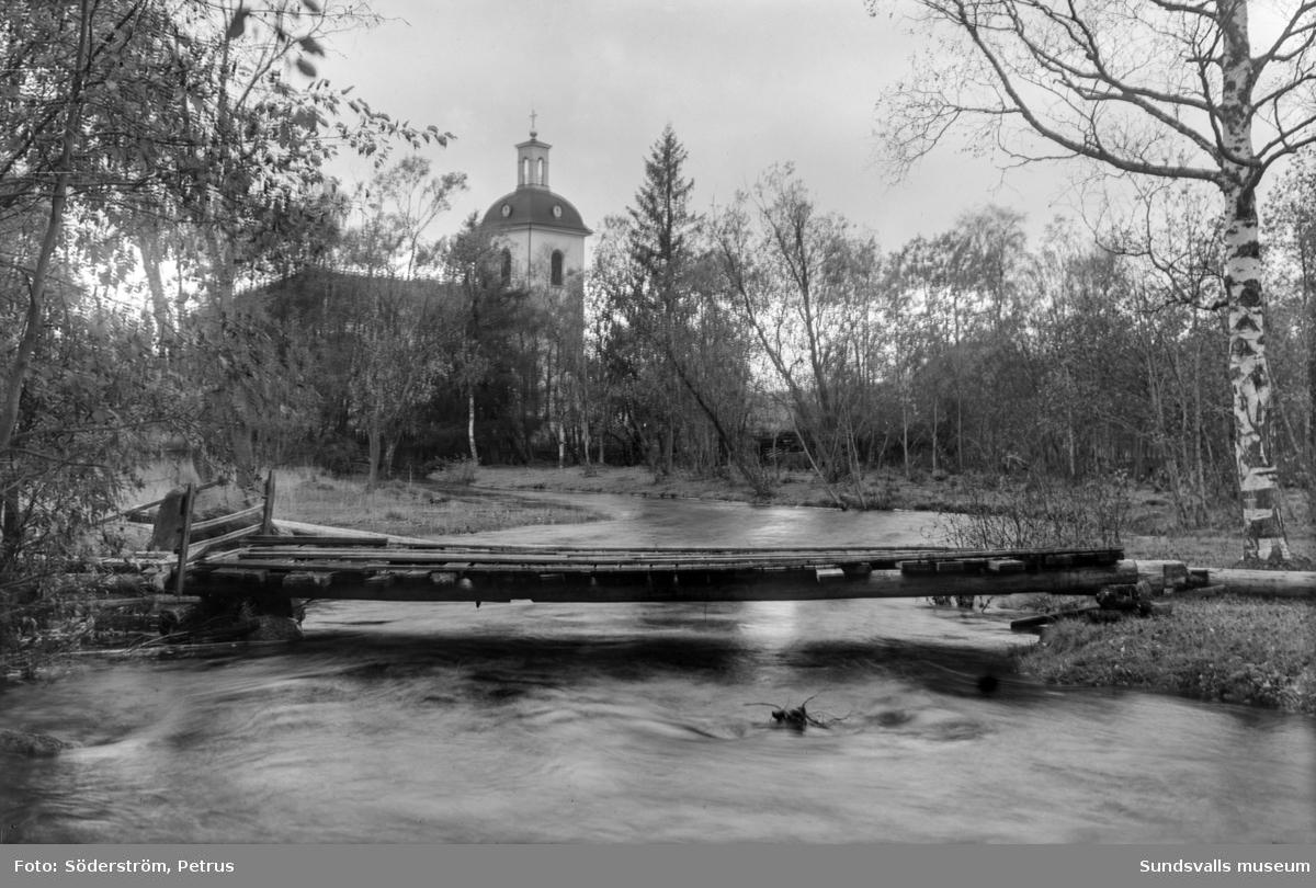 Kvarnån med bro och Indals kyrka i bakgrunden.