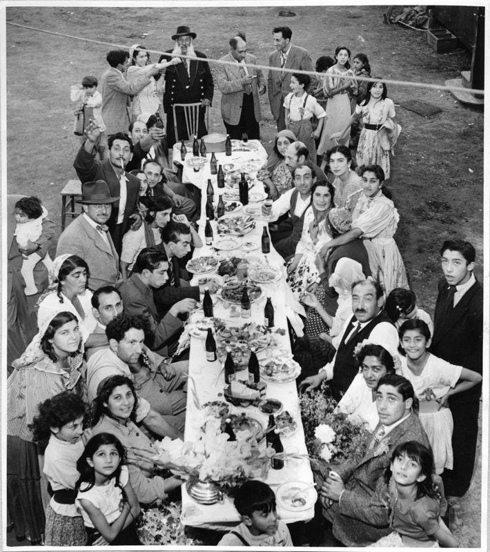 Stort romskt dubbelbröllop i Eskilstuna, troligen sommaren 1951. Långbordet är fyllt med mat, dryck  och smyckat med blommor. Många släktingar har samlats till festligheterna. Det ena av brudparen sitter på högra sidan av bordet.