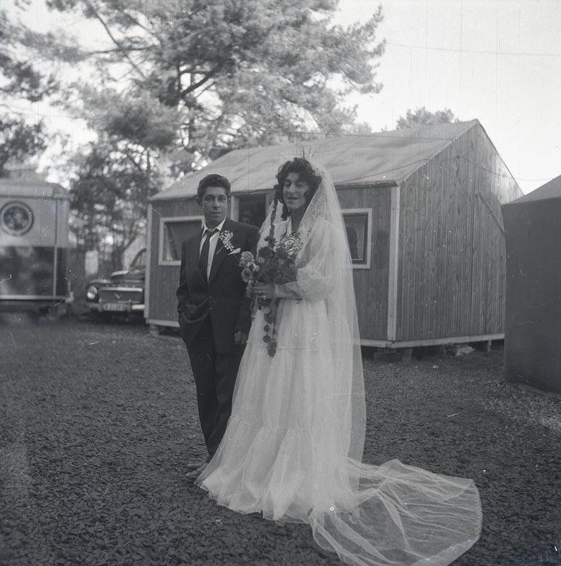 Nygift romskt par uppställda för fotografering vid bröllop i november 1958 i Nyköping. I bakgrunden syns uppställda vagnar, baracker och bilar i lägret. Svenska romer har historiskt tvingats bo i läger, ofta i samhällets utkant, då man har förvägrats fast bostad och fördrivits. Toleransen för romer har historiskt varierat mycket mellan olika samhällen, men romers närvaro har sällan setts som något positivt. Efter att de svenska romerna i Sverige erkändes som medborgare år 1952 uppstod debatt kring gruppens svåra levnadsförhållanden. En statlig utredning genomfördes under 1954-1956 där en av slutsatserna blev att fast bostad var nyckeln till att lyckas med skolgång och arbetsliv. Från och med mars 1960 hade möjlighet att rekvirera statsbidrag för kostnader i samband med romers bosättning, vilket förenklade möjligheten för svenska romer att få tillgång till permantenta bostäder samt i förlängningen studier och arbete.