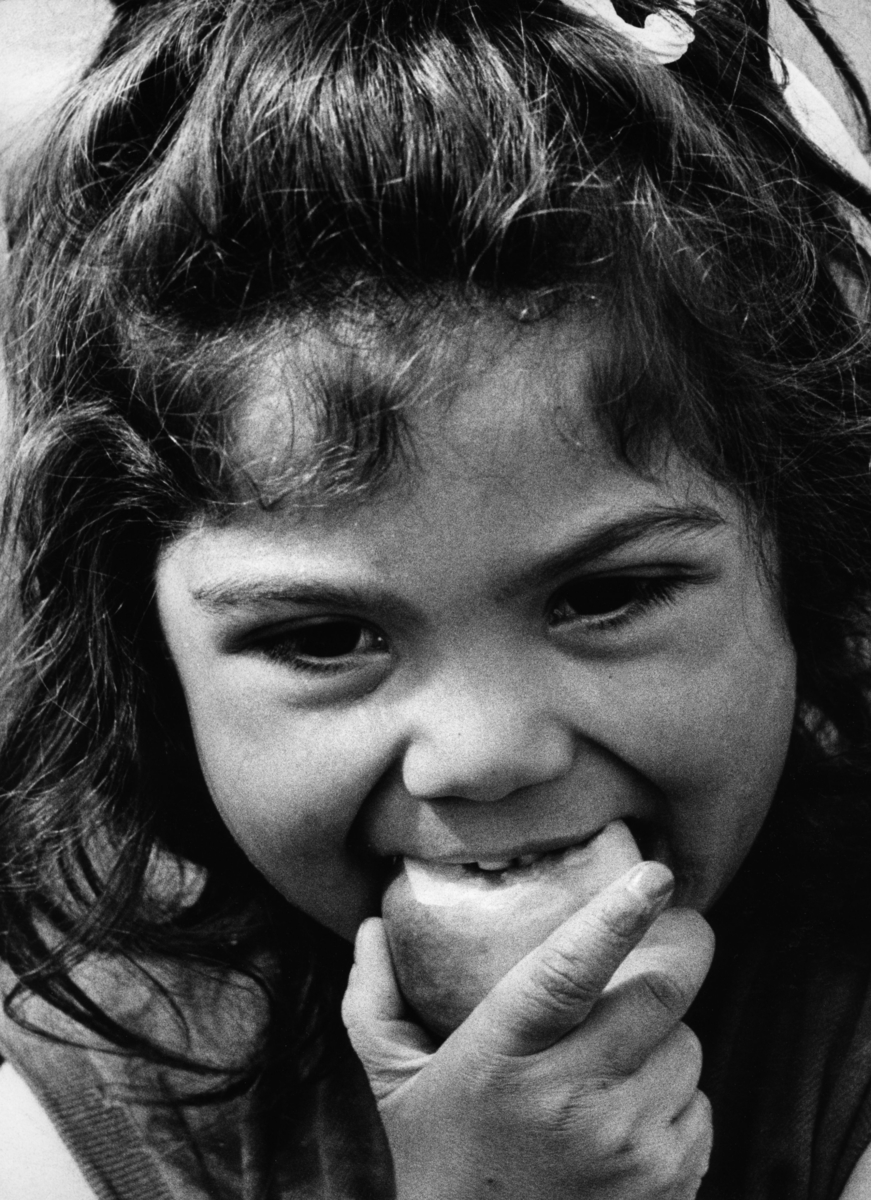 """En romsk flicka äter ett äpple. Bilden är troligen tagen i samband med inspelningen av TV-programmet """"Du svarte zigenare"""", ett program av Victor Lindgren. Programmet sändes första gången 1960-08-30."""