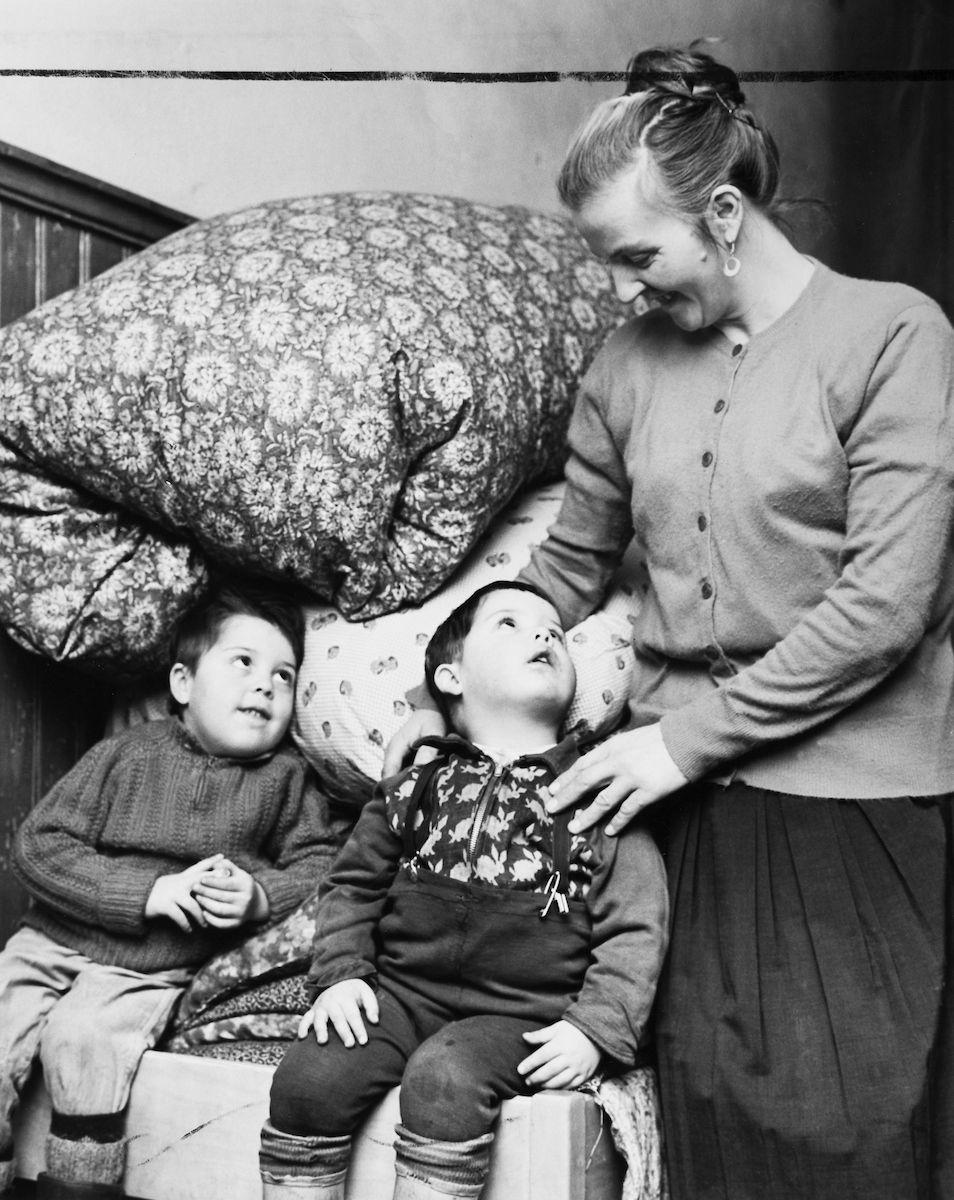 Bilden föreställer en kvinna och hennes två barn. Efter att ha levt ett kringresande liv boende i tält under flera år engagerade sig till slut en av sönernas lärarinna i familjens situation. Familjen fick under några år möjlighet att bo i en nedlagd skola i Mariefred. Efter att svenska romer erkändes som medborgare år 1952 uppstod debatt kring gruppens svåra levnadsförhållanden. En statlig utredning genomfördes under 1954-1956 där en av slutsatserna blev att fast bostad var nyckeln till att lyckas med skolgång och arbetsliv. Från och med mars 1960 hade kommuner möjlighet att rekvirera statsbidrag för kostnader i samband med romers bosättning. Frågan var dock starkt omdebatterad och processen drog ut på tiden. Efter flera år fick dock även denna familj ett eget hus att bo i.
