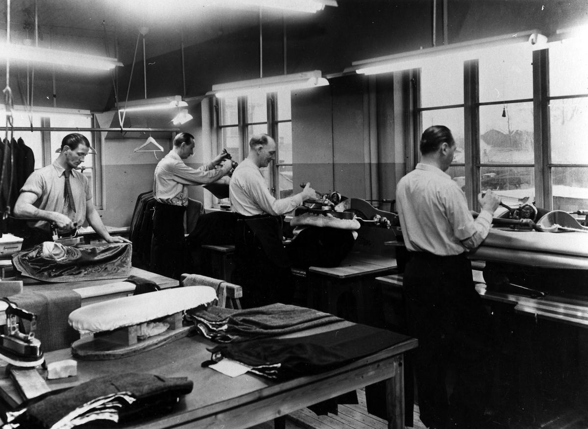 """Fyra män arbetar med pressning av byxor och kavajer. """"Pressen"""", Drabant AB."""