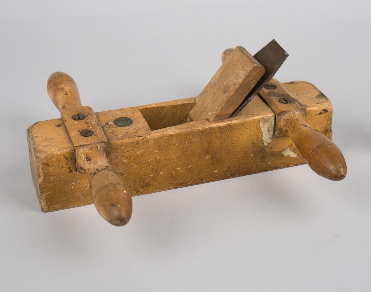 Okshøvel. Rektangulær med håndtak foran og bak som er skrudd fast til høvelen. Høveljern og kile er fastgrodd i høvel.