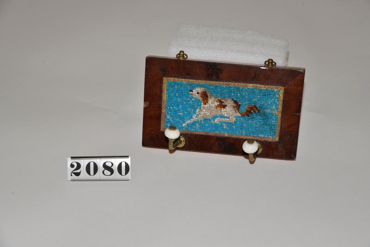 Pärlbroderat motiv i form av hund mot blå bakgrund.