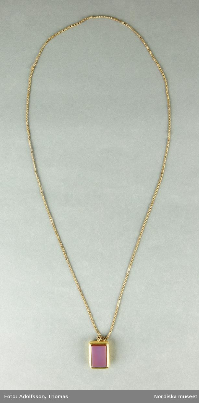 a) Medaljong, rektangulär form med rundade hörn,  hängandes på b) smal, tunn, kedja i gulmetall. Medaljongen med guldomgjärdade infällda rektangulära plattor på medaljongens fram och baksida i carneol samt onyx (?)  Medaljongen är öppningsbar på längden.  Stämplar saknas.  /Cecilia Wallquist 2019-02-15