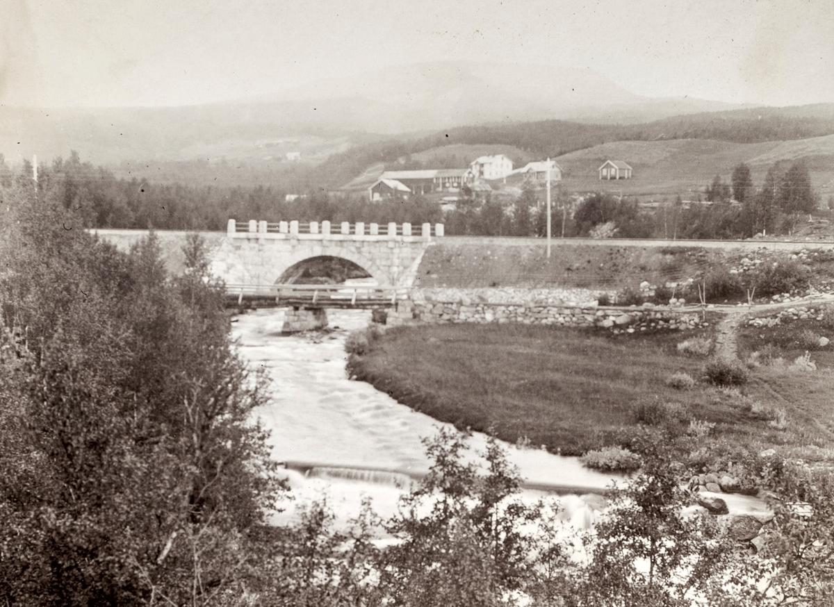 Motiv av gamle Geilo bro sammen med en nyere bro. I bakgrunnen er et større gårdsbruk.