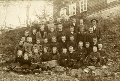 Klassebilete frå ca. 1910: «Eg hugsar vel koss bestemor og far, som høyrde til den gamle tidi i livssyn mykje, og andre som dei – rista paa hovudet til denne unge læraren som kom som eit vaarver med grundtvigianisme, maalstræv og sterke sjølvstendekrav», skreiv Olaus Islandsmoen då hans første lærar Ole O. Thorsrud vart seksti år. Thorsrud var gjennom heile livet oppteken av å lære barna «ikkje berre å ete av kunnskapstreet, men òg av livstreet», som han sa det sjølv. Biletet er frå Thorshaug skule i Bagn kring 1910, lærar Thorsrud står til høgre med hatt på hovudet. Fotograf: Kristine Thorsrud. BV 89-358C. (Foto/Photo)