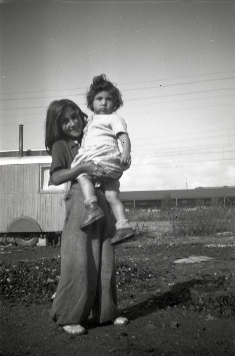 En flicka står framför en bostadsvagn med ett mindre barn i famnen. Den här bilden är troligen tagen i närheten av Göteborgs centralstation, antingen vid Bergslagsparken eller vid Kruthusgatan, där romska lägerplatser funnits på 1940- och 50-talet. I Göteborg finns flera platser runt om i staden med koppling till svenskromsk nittonhundratalshistoria. Lägerplatserna förlades ofta i vad som då var stadens ytterområden eller andra icke-planlagda områden. Romska lägerplatser även funnits bland annat i Fredriksdal och Kvillebäcksområdet (1920-talet).